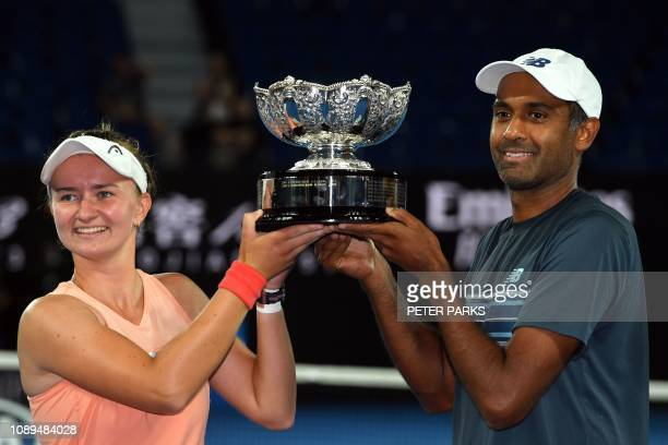 Czech Republic's Barbora Krejcikova and Rajeev Ram of the US celebrate their victory with the trophy after defeating Australia's Astra Sharma and...