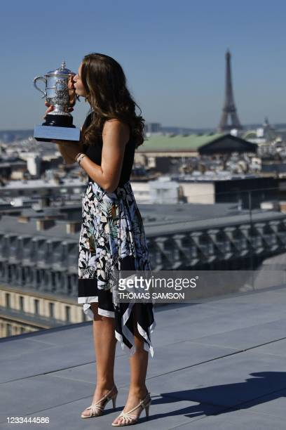 Czech Republic's Barbora Krejcikova poses with the trophy in front of the Eiffel tower, on June 14, 2021 in Paris, during a photocall two days after...