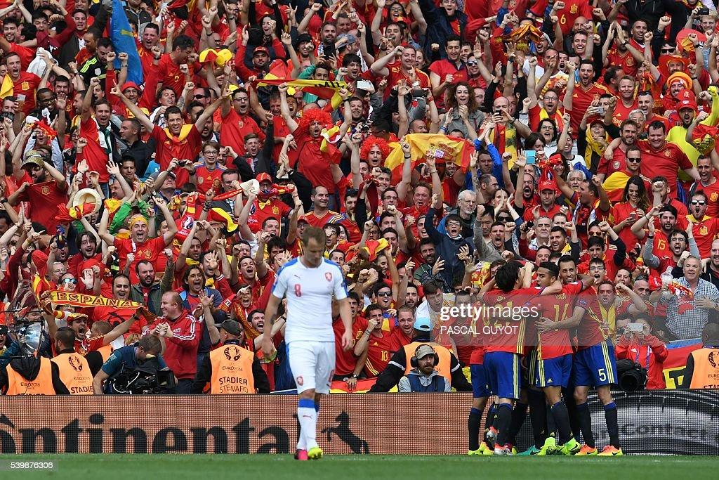 TOPSHOT - Czech Republic's defender David Limbersky walks past as Spain's players celebrate after Spain's defender Gerard Pique scored the opening goal during the Euro 2016 group D football match between Spain and Czech Republic at the Stadium Municipal in Toulouse on June 13, 2016. Spain won the match 1-0. / AFP / PASCAL
