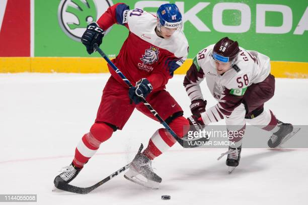 Czech Republic's forward Dominik Kubalik and Latvia's defender Guntis Galvins vie during the IIHF Men's Ice Hockey World Championships Group B match...