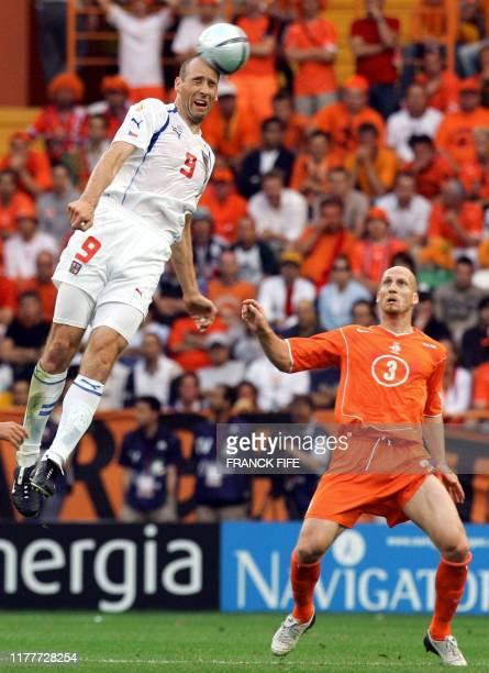 Czech Republic's forward Jan Koller head off the ball in the air undr the eyes of Netherlands' defender Jaap Stam 19 June 2004 at Aveiro's stadium...