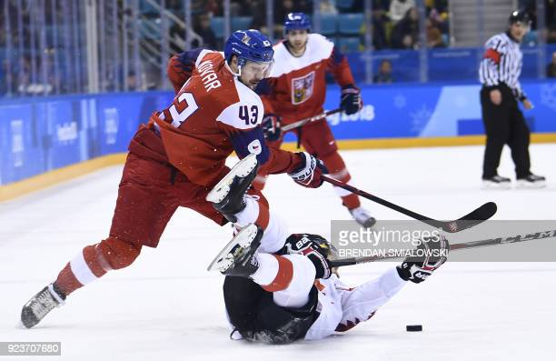 Czech Republic's Jan Kovar pushes past Canada's Brandon Kozun in the men's bronze medal ice hockey match between the Czech Republic and Canada during...