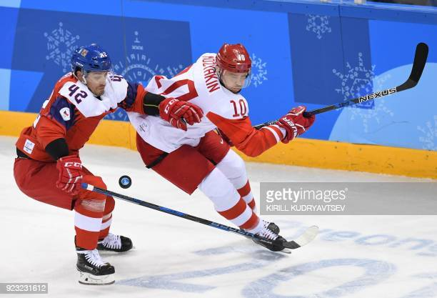 TOPSHOT Czech Republic's Petr Koukal chases the puck with Russia's Sergei Mozyakin in the men's semifinal ice hockey match between the Czech Republic...