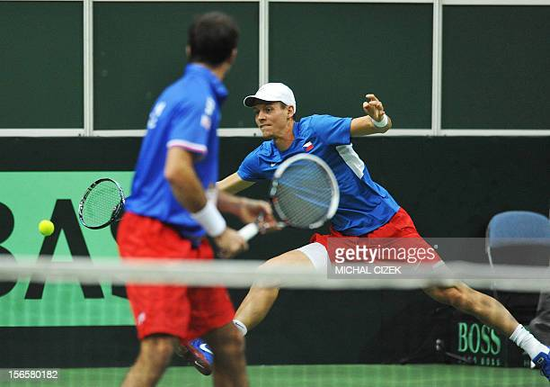 Czech Republic's player Tomas Berdych playing with Radek Stepanek returns the ball to Spanish tennis player Marcel Granollers and Marc Lopez during...