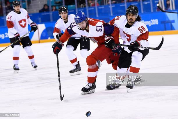 Czech Republic's Roman Horak and Switzerland's Eric Blum fight for the puck in the men's preliminary round ice hockey match between the Czech...