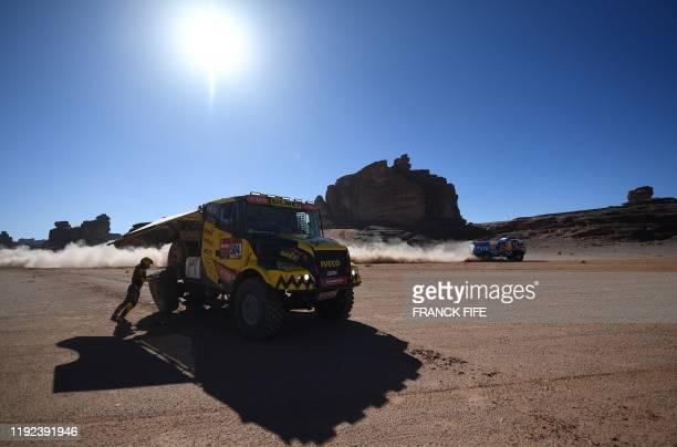 Czech Republic's truck driver Martin Macik codrivers Frantisek Tomasek and David Svanda change tyre during the Stage 3 of the Dakar 2020 around Neom...