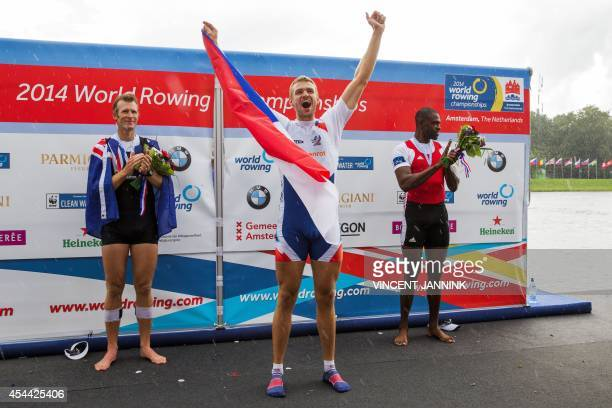 Czech rower Ondrej Synek celebrates in front of New Zealand's Mahe Drusdale and Cuba's Rodriguez Fournier after winning the Men's Single Sculls Final...