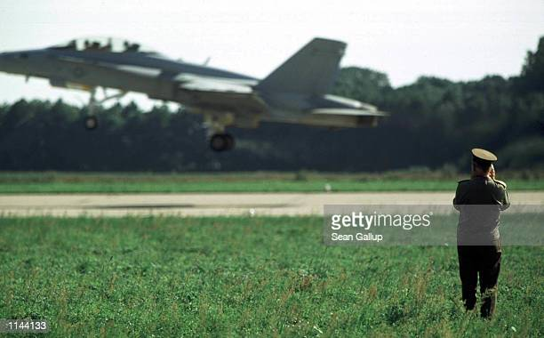 Czech soldier watches an American F/A18D Hornet take off from the Pardubice military base in the Czech Republic during a demonsstration by American...