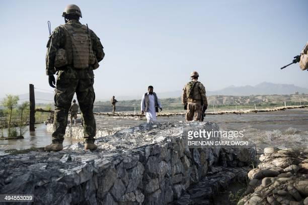 Czech soldiers walk toward a suspension bridge over a river during a patrol near Bagram Airfield in Parwan on May 29 2014 Members of the Czech Army's...