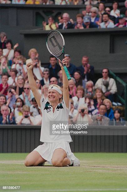 Czech tennis player Jana Novotna kneels on the court and raises her arms in the air in celebration after winning the final of the Women's Singles...