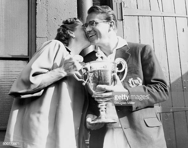 Czech tennis player Jaroslav Drobny receiving a kiss from his wife as he holds the cup following his win at Wimbledon Tennis Tournament London July...