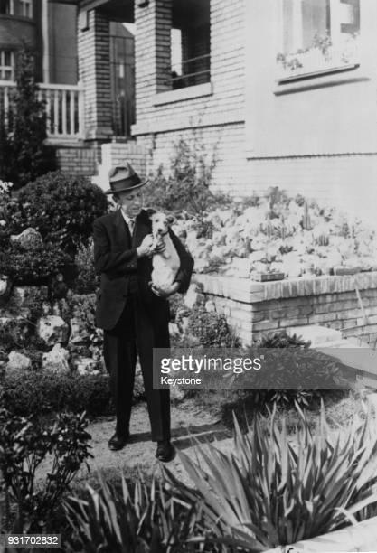 Czech writer Karel Capek in the garden of his villa in Prague Czechoslovakia with his fox terrier Dasenka circa 1933