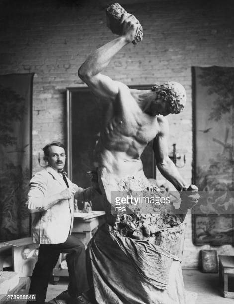 Czech-born American sculptor Albin Polasek with his sculpture 'Man Carving His Own Destiny', depicting the figure of a man chiselling himself out...