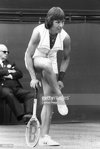 Czechborn American tennis player Martina Navratilova adjusting her shoe during a match against Jo Durie at Wimbledon