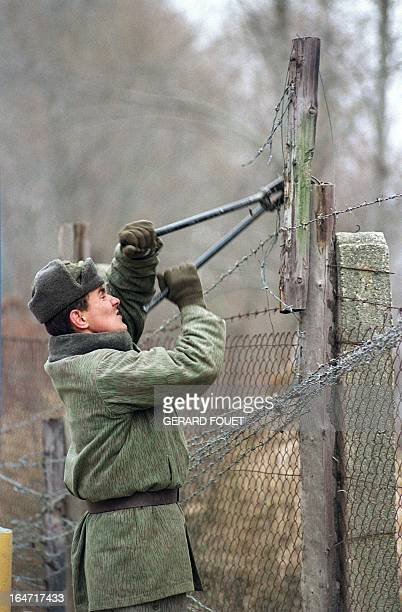 Czechoslovakian border guard dismantles the twometer high barbed wire fence along the border with Austria 11 December 1989 A strong dissident protest...