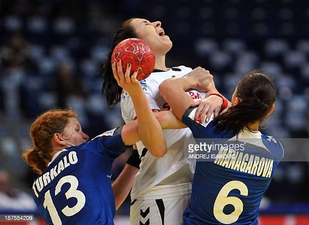 Czech's Iveta Luzumova vies with Ukraine's Natalya Turkalo and Iuliia Managarova during the Women's Euro 2012 handball championship match Ukraine vs...