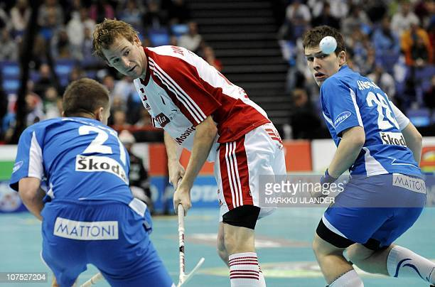 Czech's Milan Fridrich and Matej Jendrisak fight for the ball with Swiss Adrian Zimmermann during the World Floorball Championship 2010 bronze medal...