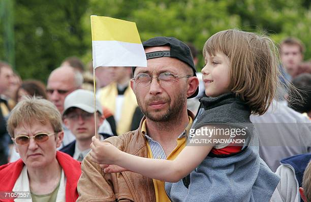 A Polish man holds his daughter looking at a vatican flag while waiting for the arrival of Pope Benedict XVI in front of Jasnagora Monastery in...