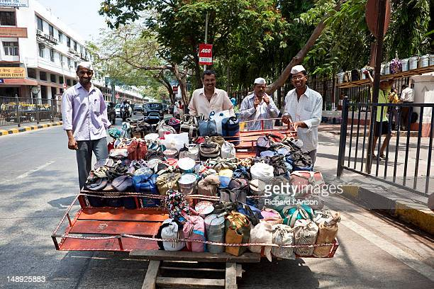dabba (food container) wallahs delivering lunch, or tiffin, boxes outside churchgate station. - tiffin box photos et images de collection