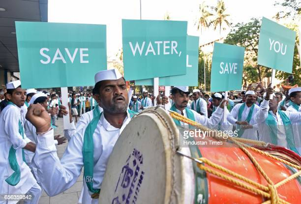 Dabbawalas participate in a flash mob for commuters to drive home the message 'save water it will save you' on the occasion of World Water Day The...