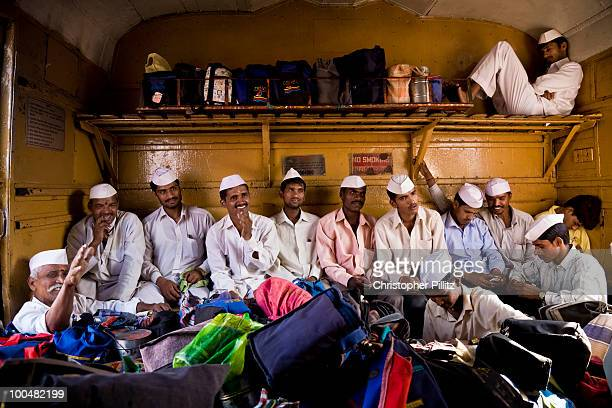 Group of Dabbawallahs travel on Mumbai's extensive rail network delivering freshly prepared home cooked food to office workers throughout Mumbai....