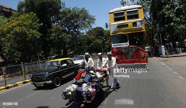 Dabbawallas walk down busy roads while delivering tiffin boxes in Mumbai, India, on Monday, May 21, 2007. Mumbai's 5,000 dabbawallas -- men who ferry...