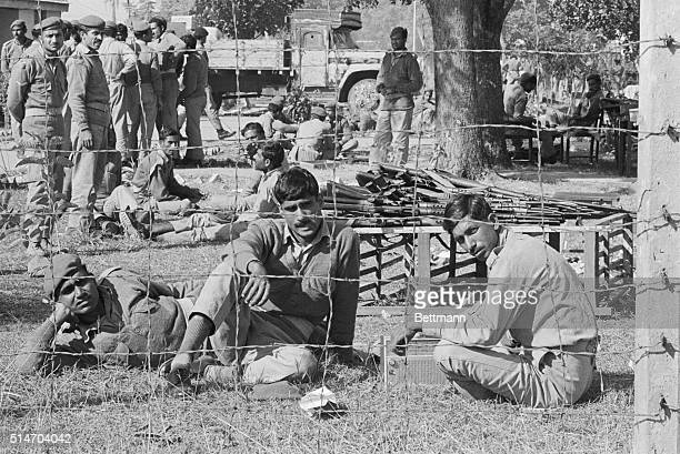 Captured Pakistani soldiers sit behind a barbed wire fence at a prison camp here The government of Pakistani Pres Yahya Khan is expected to resign...