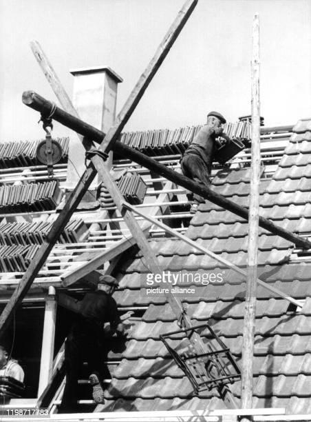 Dachdecker legen auf einem Dachstuhl neue Ziegel aus die zuvor mit einer Seilwinde aufs Dach gezogen wurden
