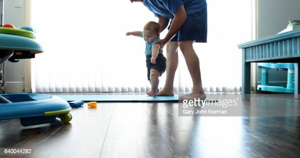 Dad and baby son ( 7-9 months) exercise at home