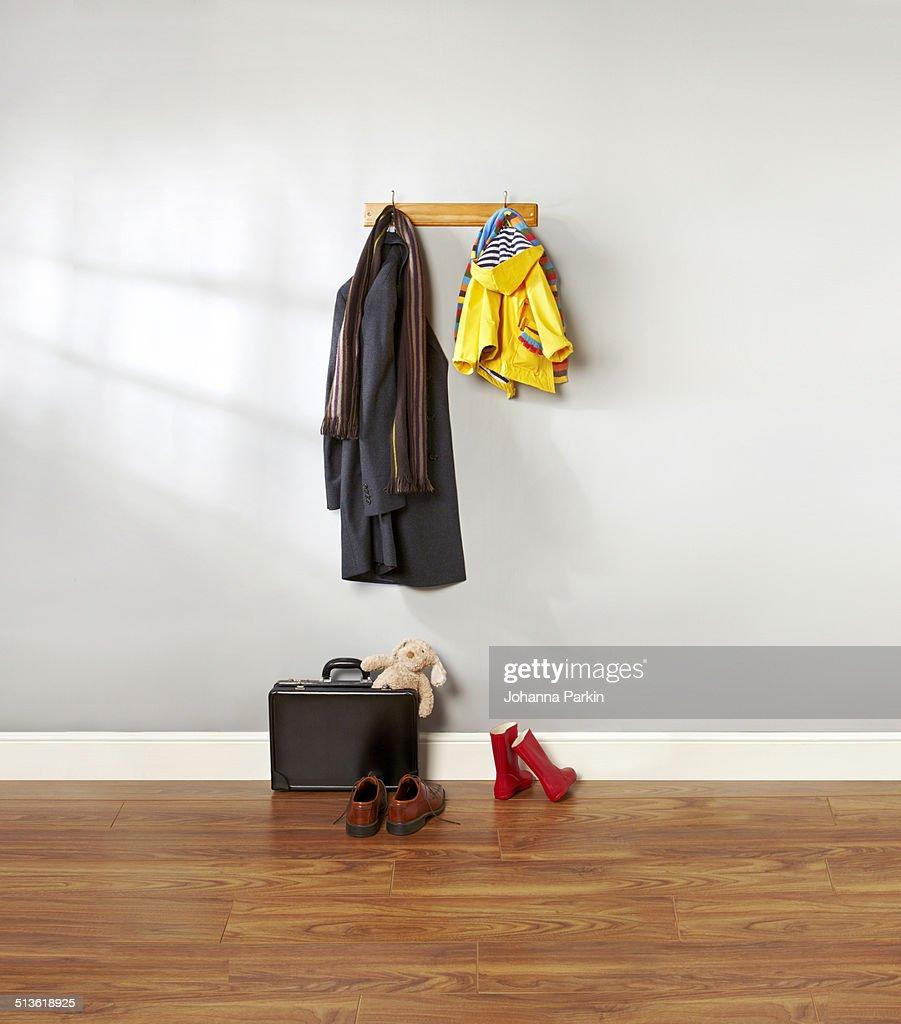 Dad and child's coat hanging up in hallway : Foto de stock