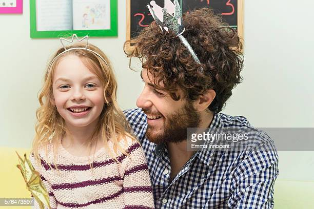 dad and cute girl with silver crowns