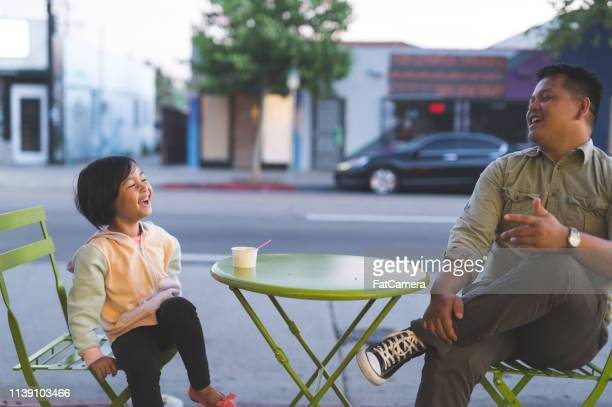 dad and daughter eating ice cream at an outdoor cafe - filipino family eating stock pictures, royalty-free photos & images