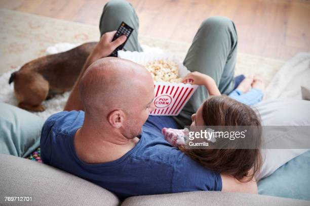 dad and daughter eating popcorn at home, over shoulder view - dog eats out girl stock photos and pictures
