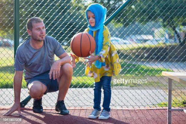 dad and daughter on a basketball court - genderblend stock pictures, royalty-free photos & images