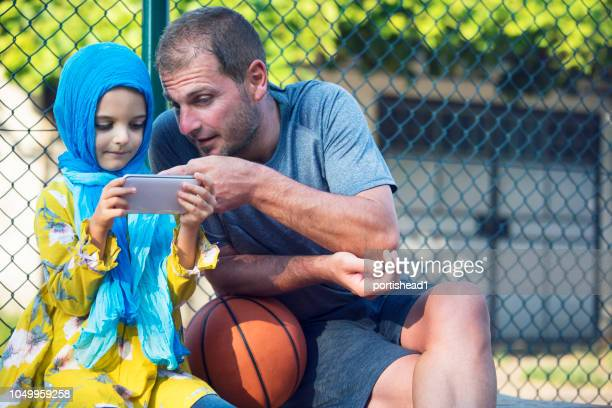 dad and daughter on a basketball court - gender bender foto e immagini stock