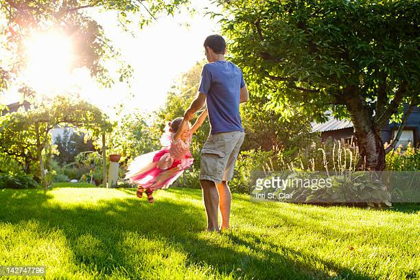 Dad and daughter (4-5) playing in garden