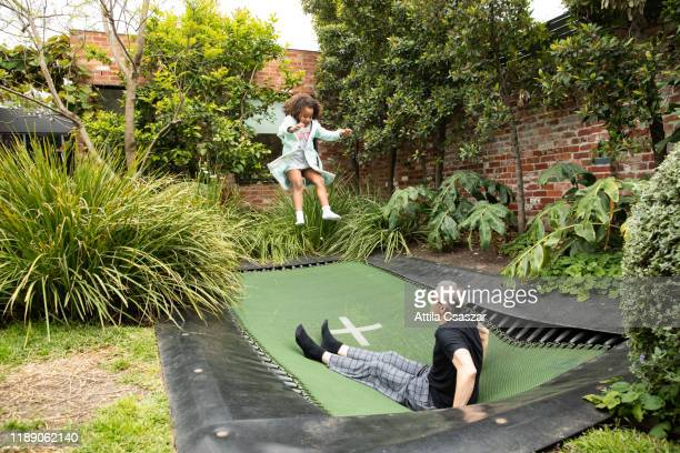 Dad and daughter playing on trampoline in garden