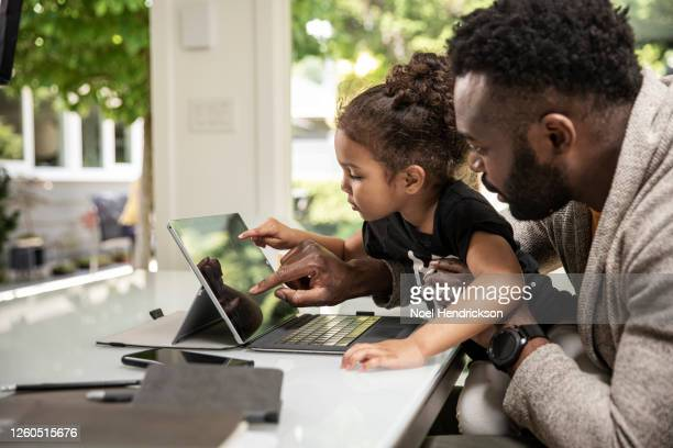 dad and daughter pointing at tablet screen - genderblend stock pictures, royalty-free photos & images
