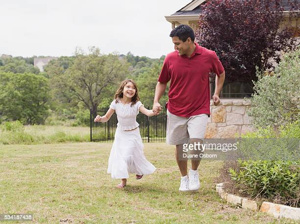 Dad and daughter running through their yard