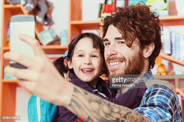 dad and daughter taking selfie, first school day