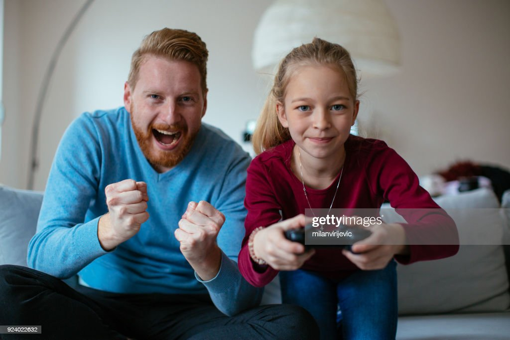 Dad and daugther playing video games : Stock Photo