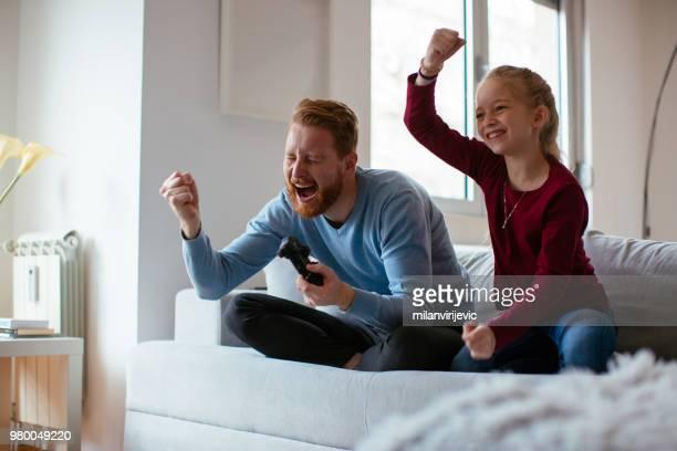 vader en dochter spelen van videospellen - commerciële activiteit stockfoto's en -beelden