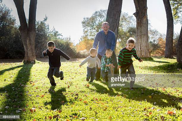 dad and four young sons running in park - single father stock photos and pictures