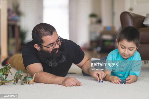 dad and his boy play with toy cars and dinosaurs in the living room - indigenous peoples of the americas stock pictures, royalty-free photos & images