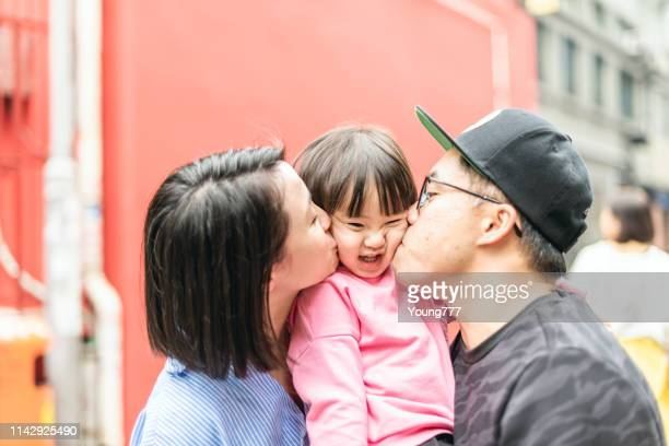 dad and mom kiss their daughter - family with one child stock pictures, royalty-free photos & images
