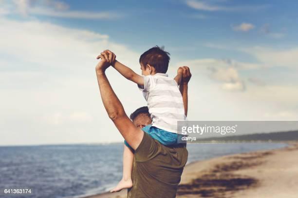 Vater und Sohn Genießen Sie den Blick aufs Meer