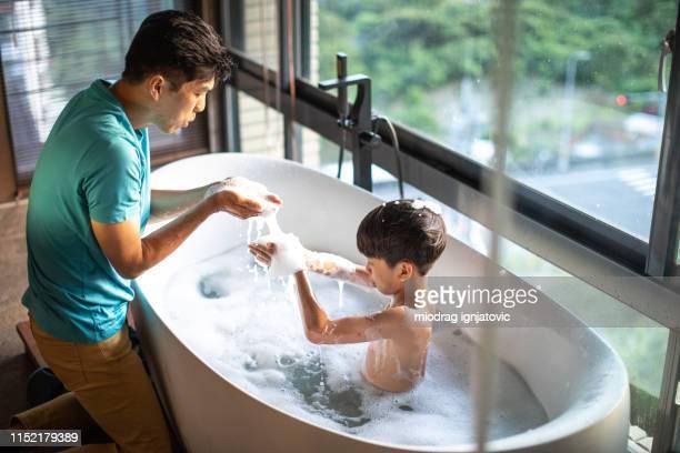 papá e hijo divirtiéndose durante el baño - chicos desnudos fotografías e imágenes de stock
