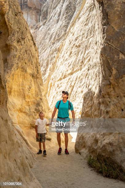 dad and son hiking in a canyon - vertical stock pictures, royalty-free photos & images