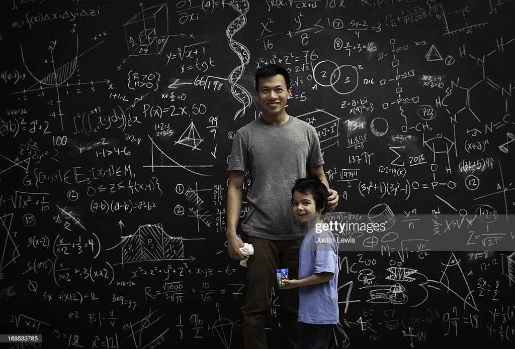 Dad and son in front of math covered chalkboard : Stock Photo