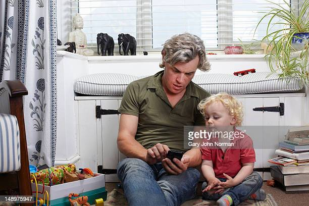 dad and son looking at mobile phone
